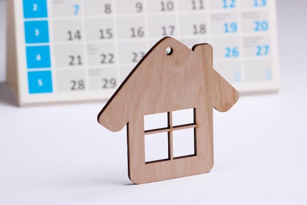 白い背景の上のデスクトップカレンダーとミニフィギュアの家。家賃支払いのコンセプト