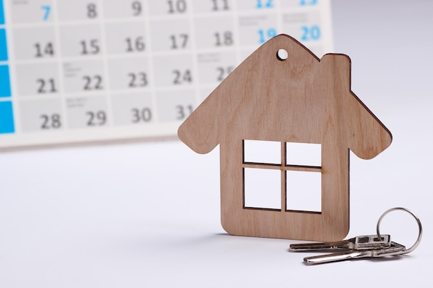 Мини-фигура дом с настольным календарем на белом фоне. концепция оплаты арендной платы за жилье