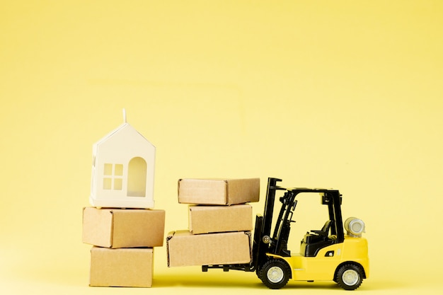 Mini forklift truck load cardboard boxes in the airplane. fast delivery of goods and products.