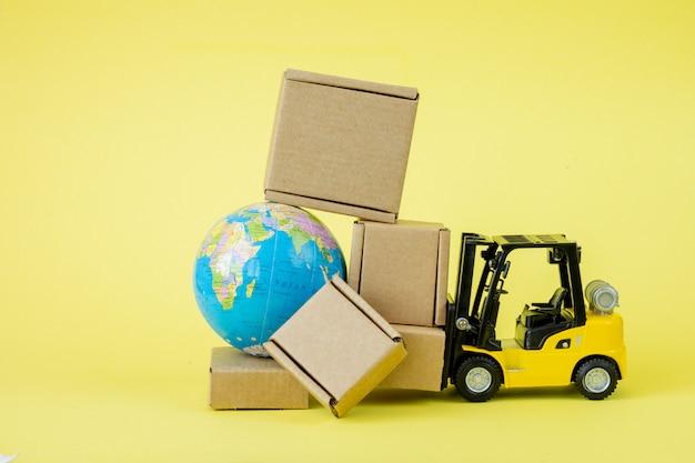 미니 지게차 적재 판지 상자. 상품 및 제품의 빠른 배송. 물류, 도달하기 어려운 장소와의 연결. 배너, 복사 공간.