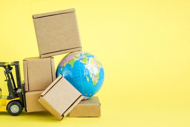 미니 지게차는 판지 상자를 적재합니다. 상품 및 제품의 빠른 배송. 물류, 접근하기 어려운 곳으로 연결. 배너, 복사 공간입니다.
