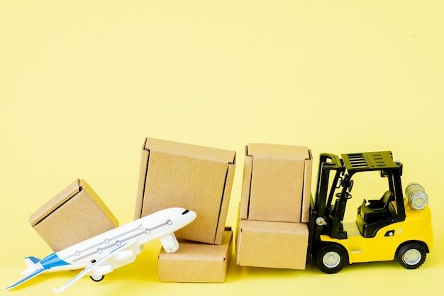 미니 지게차는 비행기에 판지 상자를 싣습니다. 상품 및 제품의 빠른 배송. 물류, 접근하기 어려운 곳으로 연결. 배너, 복사 공간입니다. 프리미엄 사진