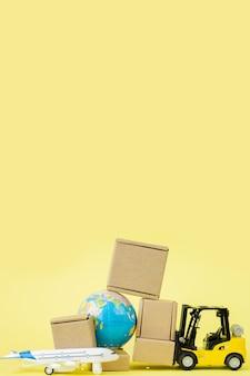 미니 지게차는 비행기에 판지 상자를 싣습니다. 상품 및 제품의 빠른 배송. 물류, 접근하기 어려운 곳으로 연결. 배너, 복사 공간입니다.