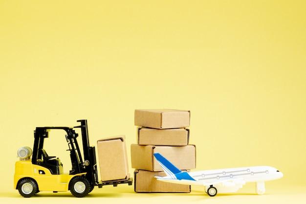 미니 지게차는 비행기에 판지 상자를 적재합니다. 상품 및 제품의 빠른 배송.