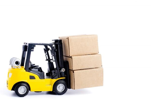 ミニフォークリフトトラックは、白い背景で隔離の段ボール箱を読み込みます。ロジスティクスと輸送管理のアイデアと業界のビジネス商業コンセプト。