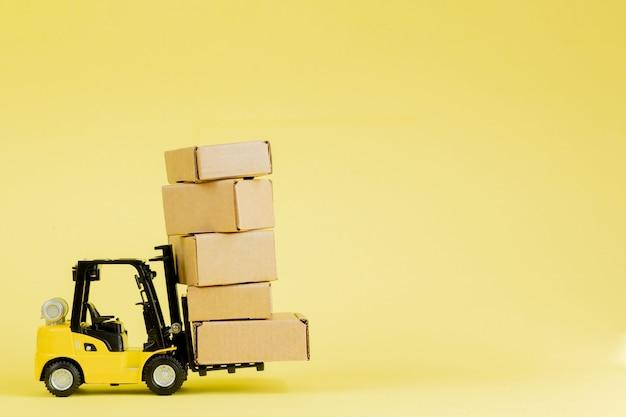 미니 지게차는 판지 상자를 적재합니다. 물류 및 운송 관리 아이디어와 산업 비즈니스 상업 개념.
