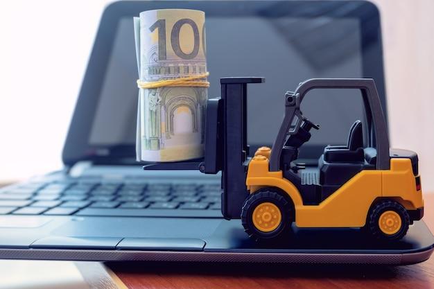 미니 지게차는 노트북 키보드에 지폐를 적재합니다. 물류, 운송, 관리 아이디어, 산업 비즈니스 상업 개념.
