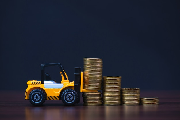 Mini forklift truck loading stack coin with steps of gold coin in dark,