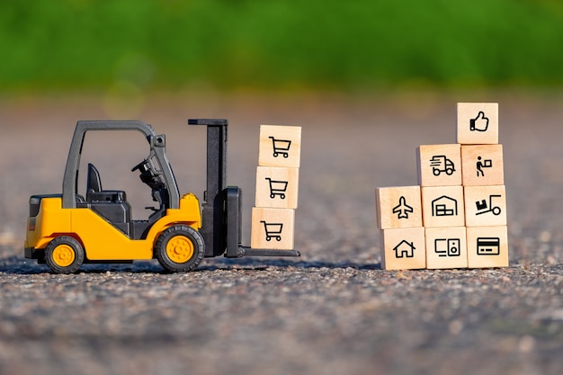 Mini forklift truck moves a pallet with wooden block with icons