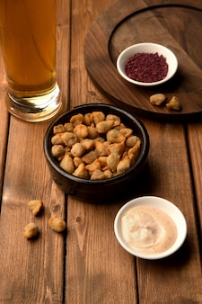 Mini fried dumplings as beer snack served with sauce and sumac