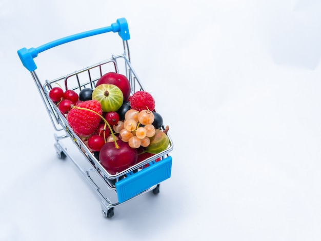 分離された新鮮なビタミンベリーで満たされたミニ食料品のカート。