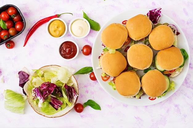 Мини-гамбургеры с куриным гамбургером, сыром и овощами. квартира лежала. вид сверху.