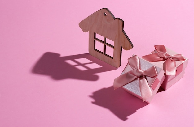 Mini house figure and gift box on pink pastel background. studio shot with shadow