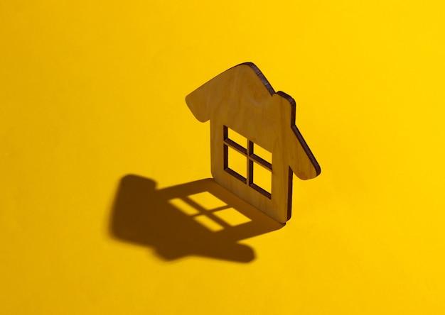 黄色の背景にミニハウスフィギュア。影付きのスタジオ撮影