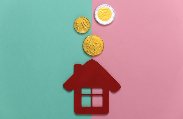 Mini house figurine with coins on a blue-pink pastel. family budget
