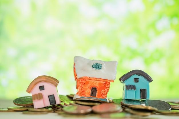 Мини дом на кучу монет с зеленым размытия.