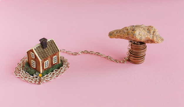 Mini house on pink is shrouded in chain and a heavy stone lies on the chain and near keys to the house.