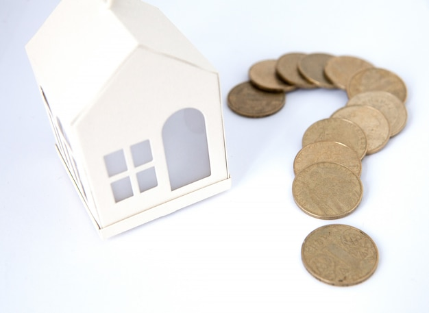 Mini house on stack of coins. concept of investment property