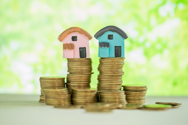 Mini house on stack of coins with green blur.