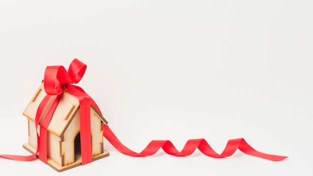 Mini house tied with red ribbon against white backdrop