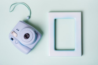 Mini instant camera and empty border frame on blue background