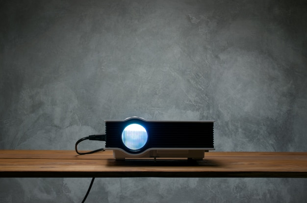 Mini led projector on wood table in a room projector home theater concept.