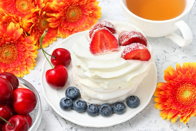 Mini meringue with whipped cream cake decorated with fresh fruits with gerbera flowers