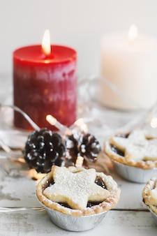 Мини-пирожки с фаршем, подаваемые с красной и белой свечой, сосновыми шишками и декоративными огнями