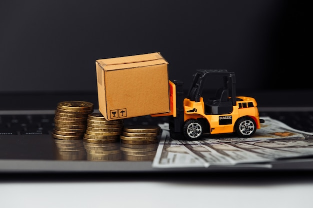 Mini model of forklift with boxes on laptop close-up