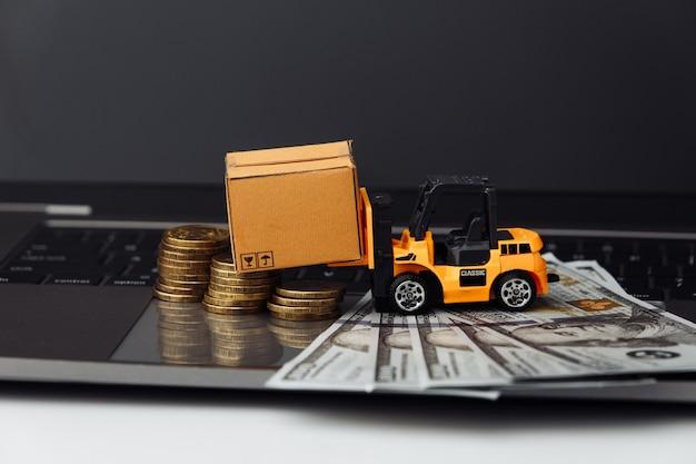 Мини-модель погрузчика с ящиками и деньгами на клавиатуре.