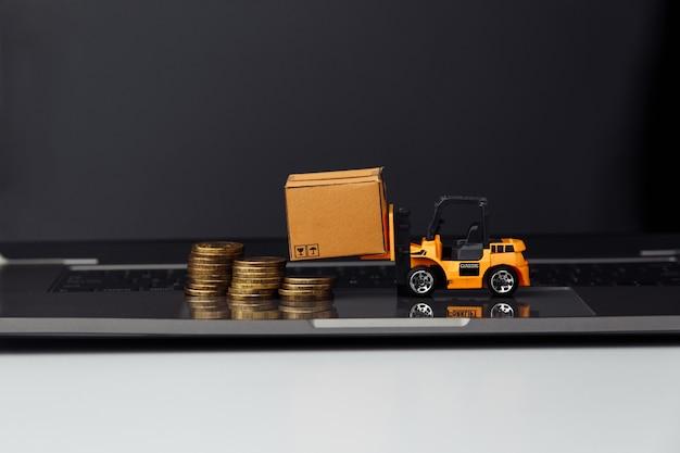 노트북에 상자와 지게차의 미니 모델. 물류 및 도매 개념.