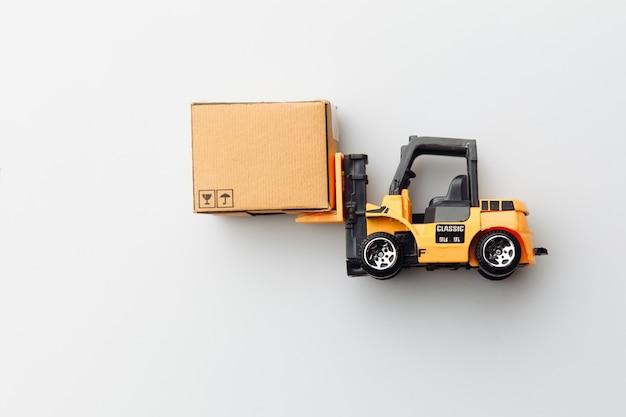 白で隔離のカートンボックスとフォークリフトのミニモデル。ロジスティクスと配送のコンセプト。上面図