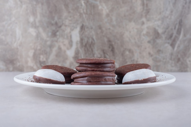 Mini mousse di pasticceria e biscotto ricoperto di cioccolato dessert su un piatto sul tavolo di marmo.