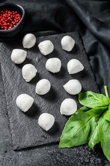 Мини сырные шарики из моцареллы на каменной доске с листьями базилика и розовым перцем. черный фон. вид сверху