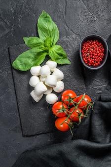 Мини сыр моцарелла, листья базилика и помидоры черри, приготовление салата капрезе. черный фон. вид сверху