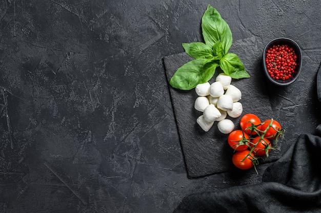 Мини сыр моцарелла, листья базилика и помидоры черри, приготовление салата капрезе. вид сверху. копировать пространство