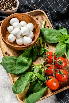 Mini mozzarella cheese, basil leaves and cherry tomatoes, cooking caprese salad. gray background. top view