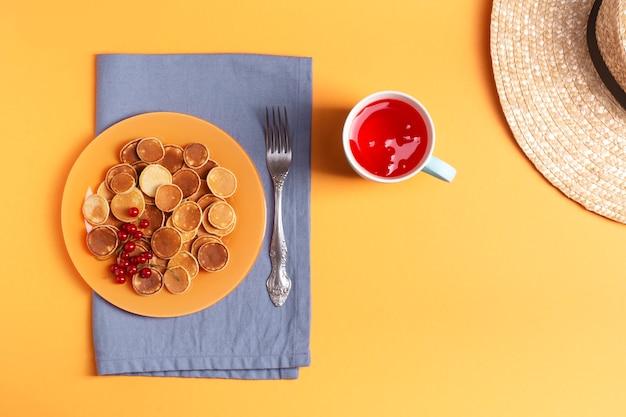 青いナプキンの上にオレンジ色のプレートのミニパンケーキが立っています