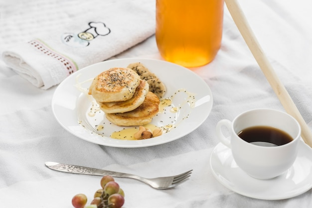 Mini pancakes with banana; honey and chia seeds on plate