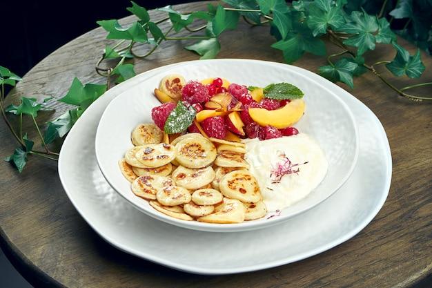 木の表面に白いプレートにフルーツとヨーグルトのミニパンケーキ。朝食においしい料理