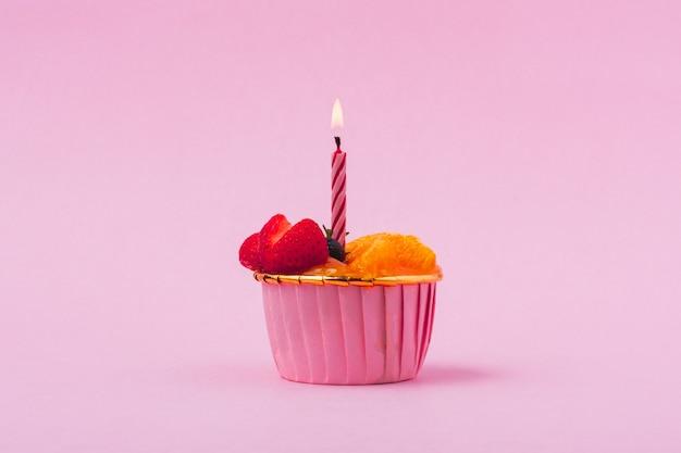 불타는 촛불과 과일 또는 오렌지 스폰지 케이크의 미니 종이 컵