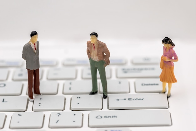 Mini people on a computer keyboard