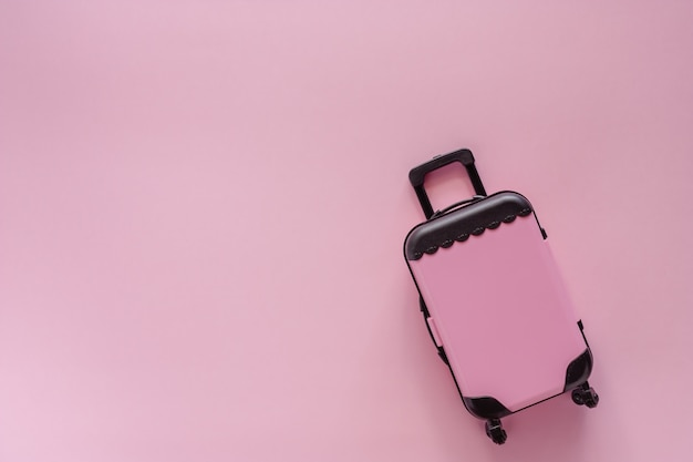Mini pinky luggage toy model on pinky pastel colored background for traveling