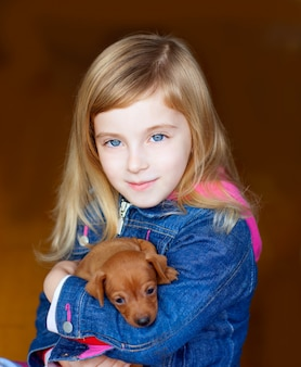 Mini pinnscher puppy mascot with blond kid girl