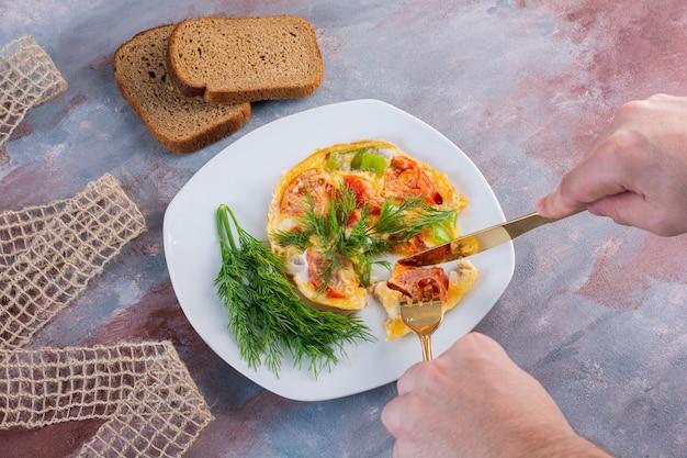 大理石の表面のフォークとパンの隣の皿にミニピザ