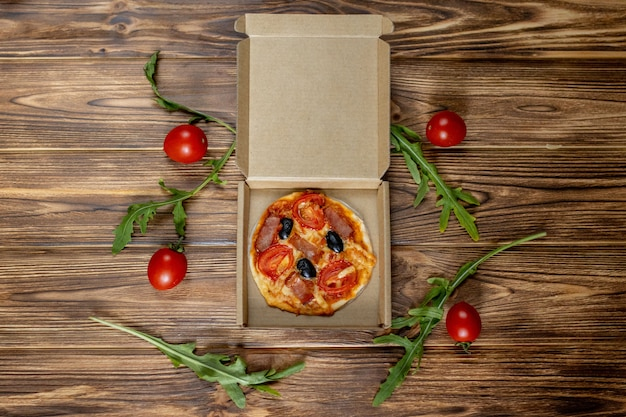 Mini pizza prepared by a child with tomatoes, olives and ham on a wooden background