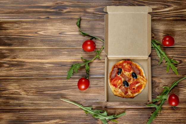 Mini pizza prepared by a child with tomatoes, olives and ham on a wooden background.