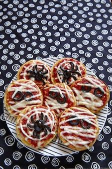 ハロウィーンのためにクモとミイラで飾られたミニピザ