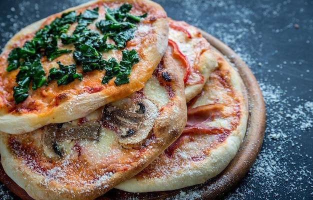 Мини-пицца с различными начинками на деревянной доске