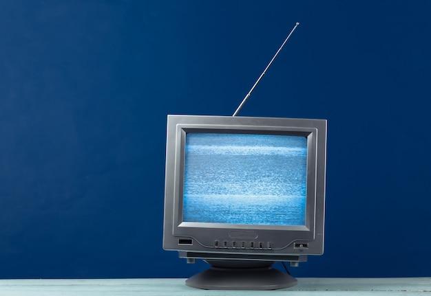 Mini retro tv antenna receiver on classic blue. old fashioned tv set. television noise